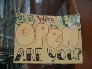 hand-lettered sign reading We're Open Are You