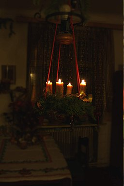 Advent wreath with four candles lit in a darkened space