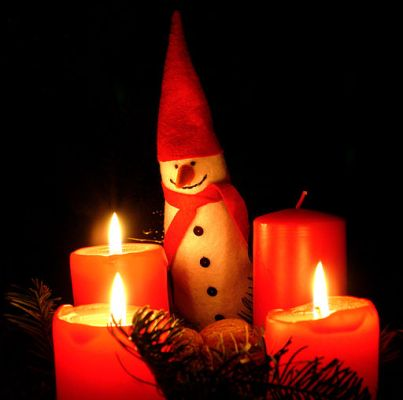 three lit Advent candles with figurine