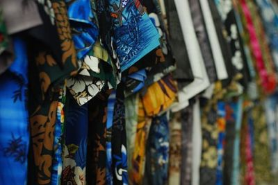 Aloha shirts in varied colors hanging on a rack