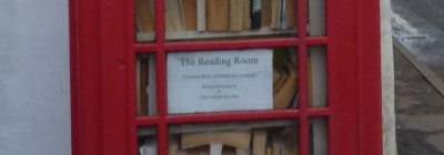 "A sign in a red British telephone kiosk being used as a book exchange that reads ""The Reading Room: Paperback Book and Magazine exchange, Bring something in and take something away"""