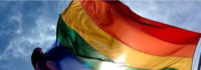 portion of rainbow flag fluttering against blue sky