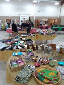 tables displaying bazaar items, quilt, people, in church meeting hall