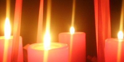 four candles alight against a dark background