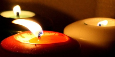 three lighted candles in the dark