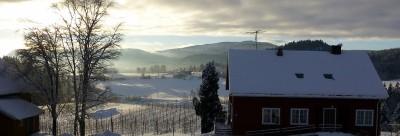 farmhouse in snow as dawn breaks on the horizon
