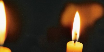 two lit candles against a dark background