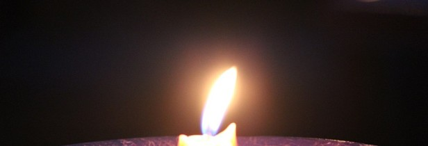 single candle flame in darkness