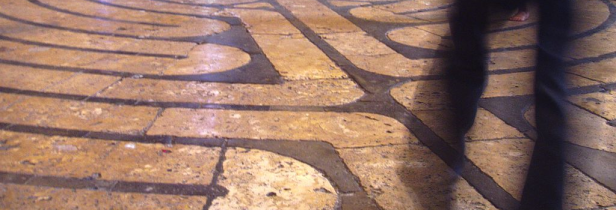 a portion of the labyrinth inset in the floor of Chartres cathedral, with a walker