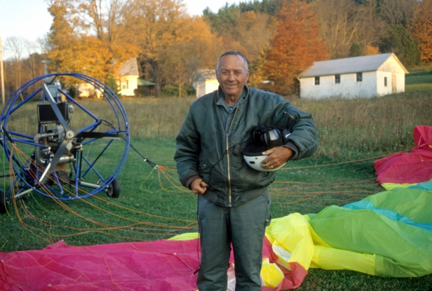 Warren Moses standing in a field in front of a brightly colored parachute and flying apparatus