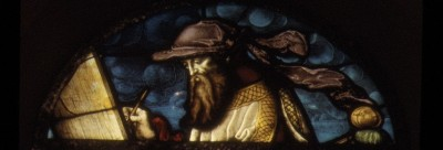 Stained glass image of Prophet Isaiah composing a text
