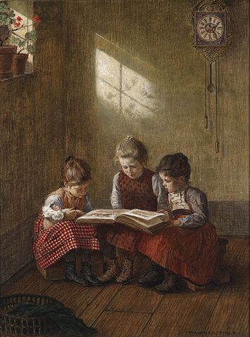 three young girls sitting in a room reading a large book