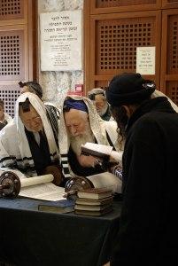 men in prayer shawls discuss torah at western wall Jerusalem