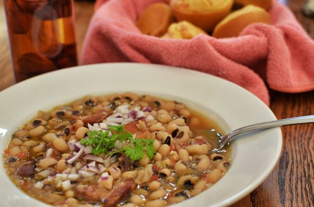 bowl of black-eyed peas on a table with onion and parsley garnish