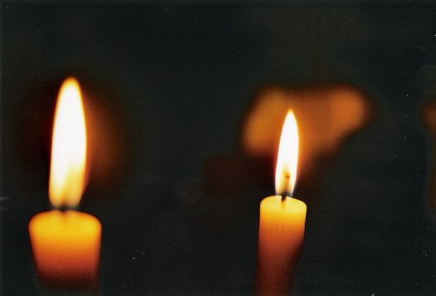 two lighted candles in the dark