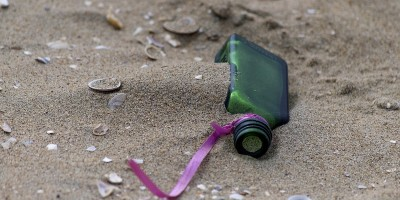 small green bottle with ribbon attached lying on a sandy beach